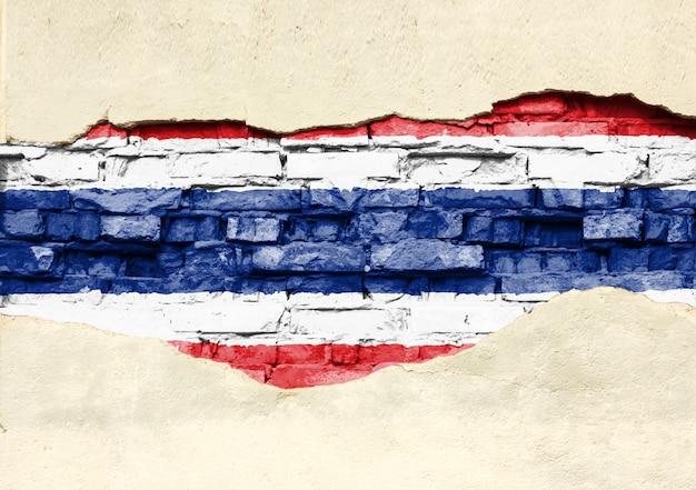 Bandera nacional de tailandia sobre un fondo de ladrillo. pared de ladrillo con yeso, fondo o textura parcialmente destruidos.