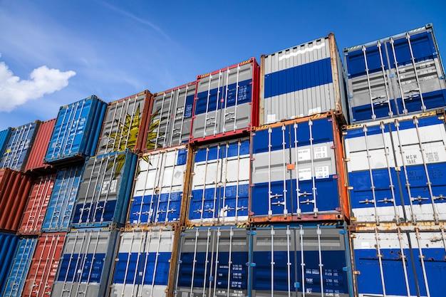 Bandera nacional de uruguay en una gran cantidad de contenedores metálicos para almacenar mercancías apiladas en filas