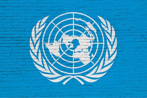 La bandera de las naciones unidas pintada en la pared de ladrillo.