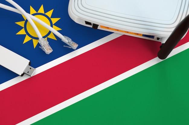 Bandera de namibia representada en la mesa con cable de internet, adaptador wifi usb inalámbrico y enrutador. concepto de conexión a internet