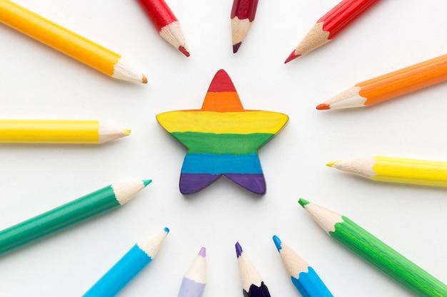 Bandera del orgullo del arco iris hecha de lápices y estrella en el medio