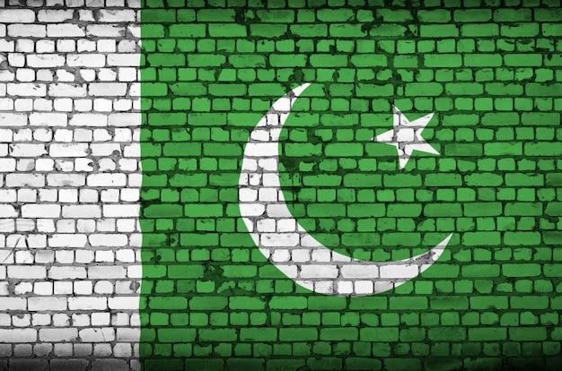 La bandera de pakistán está pintada en una vieja pared de ladrillo
