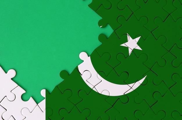 La bandera de pakistán se representa en un rompecabezas completo con espacio libre de copia verde en el lado izquierdo