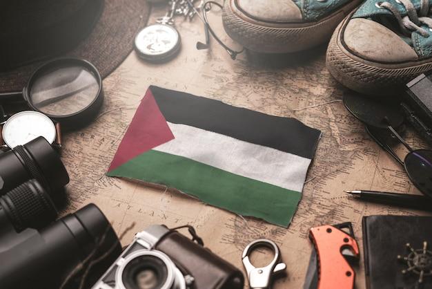 Bandera de palestina entre los accesorios del viajero en el viejo mapa vintage. concepto de destino turístico.