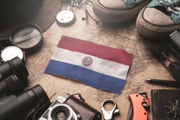 Bandera de paraguay entre los accesorios del viajero en el viejo mapa vintage. concepto de destino turístico.