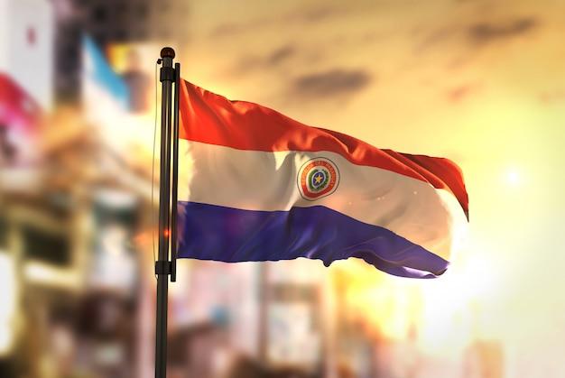 Bandera de paraguay contra la ciudad borrosa de fondo a la salida del sol