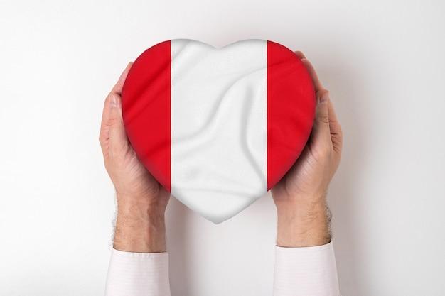 Bandera de perú en una caja en forma de corazón en manos masculinas. blanco