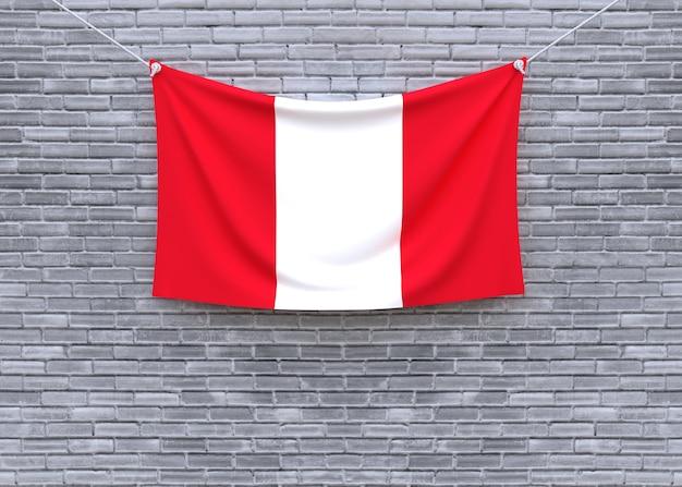 Bandera de perú colgando en la pared de ladrillo