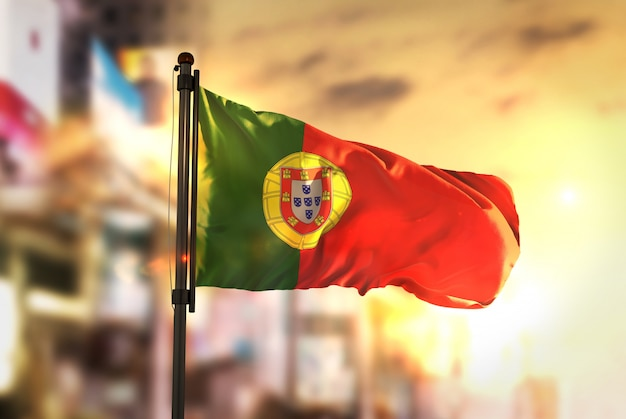 Bandera de portugal contra la ciudad borrosa de fondo a la salida del sol