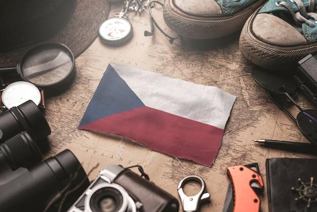 Bandera de la república checa entre los accesorios del viajero en el viejo mapa vintage. concepto de destino turístico.