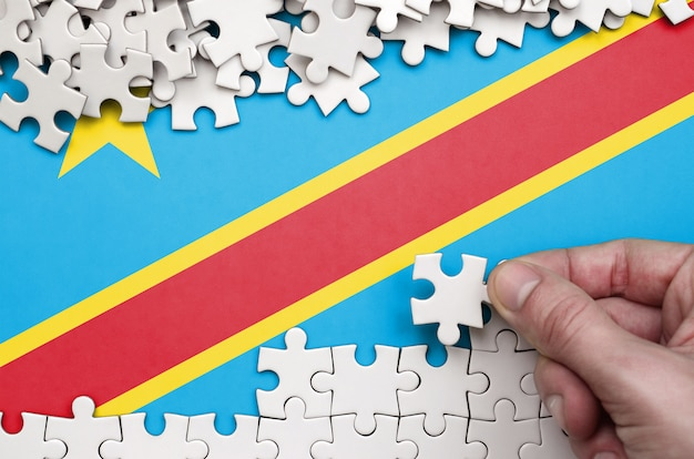 La bandera de la república democrática del congo está representada en una mesa en la que la mano humana dobla un rompecabezas de color blanco.