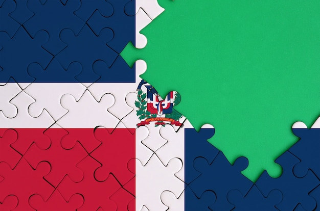 La bandera de la república dominicana se representa en un rompecabezas completo con espacio de copia verde gratis en el lado derecho