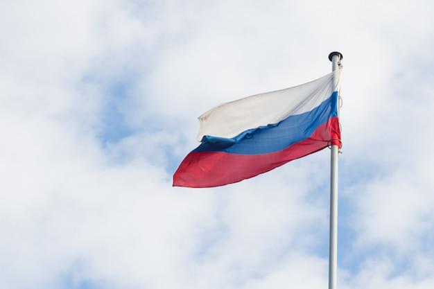 La bandera rusa ondea en el viento contra el cielo azul.