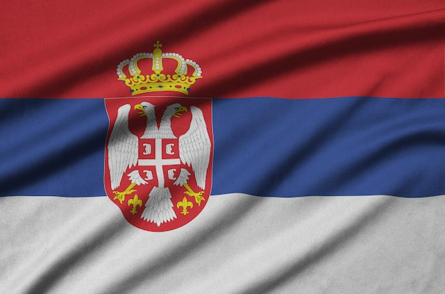 La bandera de serbia está representada en una tela de tela deportiva con muchos pliegues.