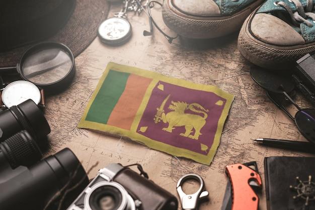 Bandera de sri lanka entre los accesorios del viajero en el viejo mapa vintage. concepto de destino turístico.