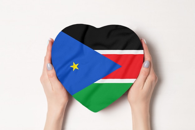 Bandera de sudán del sur en una caja en forma de corazón en manos femeninas.