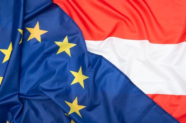 Bandera de tela natural de austria y la bandera de la unión europea de la ue como textura o fondo