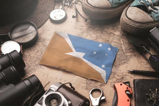 Bandera de tierra del fuego entre los accesorios del viajero en el viejo mapa vintage. concepto de destino turístico.