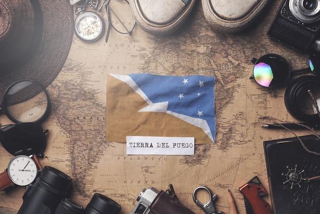 Bandera de tierra del fuego entre los accesorios del viajero en el viejo mapa vintage. tiro de arriba