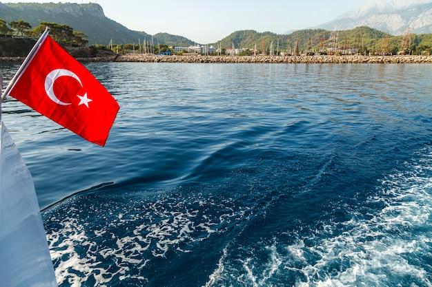 Bandera turca volando en el viento contra el fondo del mar y la costa