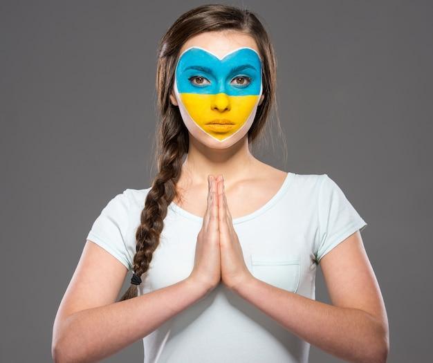 Bandera de ucrania pintada en la cara de la mujer hermosa joven.