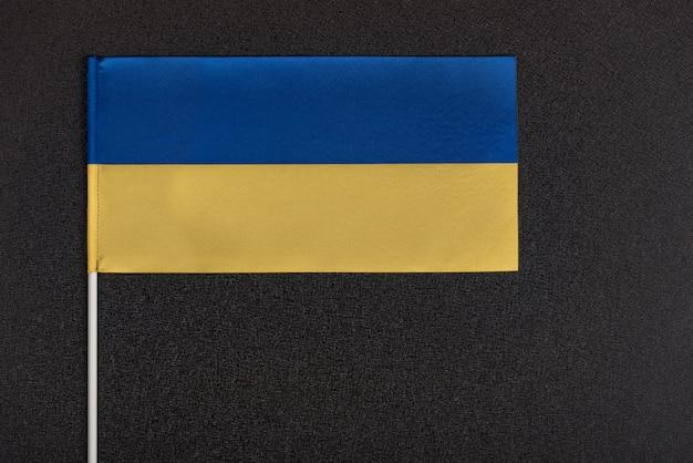 Bandera de ucrania sobre fondo negro. símbolos nacionales de ucrania. bandera amarilla y azul de cerca