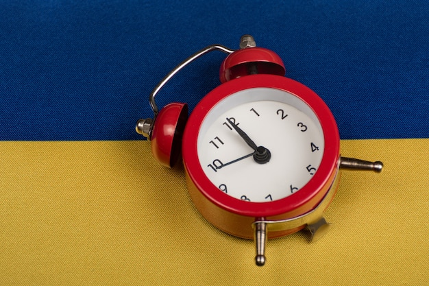 Bandera ucraniana y despertador vintage, de cerca. hora de aprender ucraniano. hora de viajar por ucrania