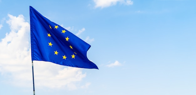 Bandera de la unión europea contra el cielo azul que agita