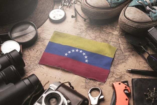 Bandera de venezuela entre los accesorios del viajero en el viejo mapa vintage. concepto de destino turístico.