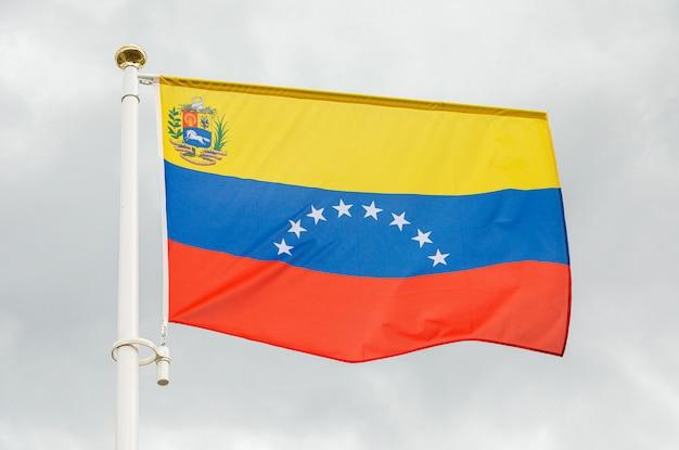 Bandera de venezuela contra el cielo nublado blanco