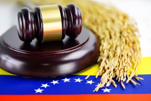 La bandera de venezuela y el juez martillan con arroz de grano dorado.