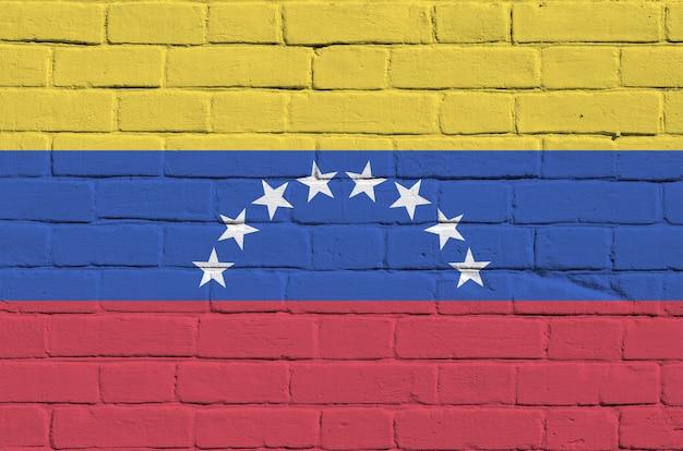 Bandera de venezuela representada en colores de pintura en la pared de ladrillo antiguo. banner con textura sobre fondo de mampostería de pared de ladrillo grande