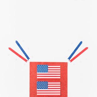 Banderas y cintas de estados unidos sobre terciopelo rojo.