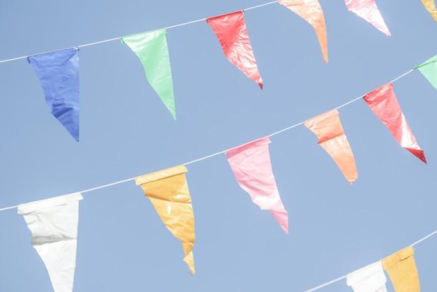 Banderas coloridas del partido del empavesado que cuelgan en el cielo azul para la decoración del día de fiesta