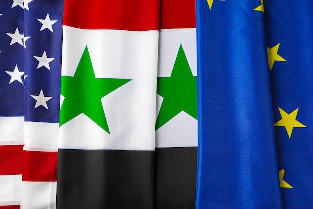 Banderas de estados unidos, siria y la ue juntas