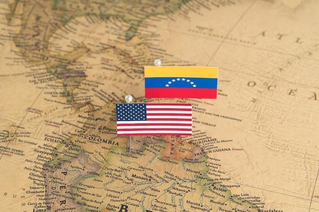 Banderas de estados unidos y venezuela en el mapa del mundo. fotografía conceptual, política y orden mundial