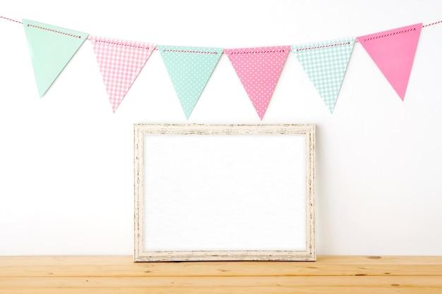 Banderas de fiesta colorido colgando sobre el marco de madera blanco vintage en blanco