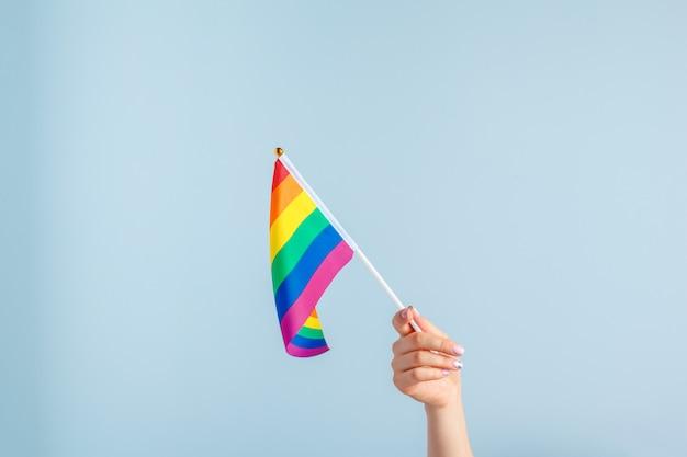 Banderas gay en mano de mujer en gris