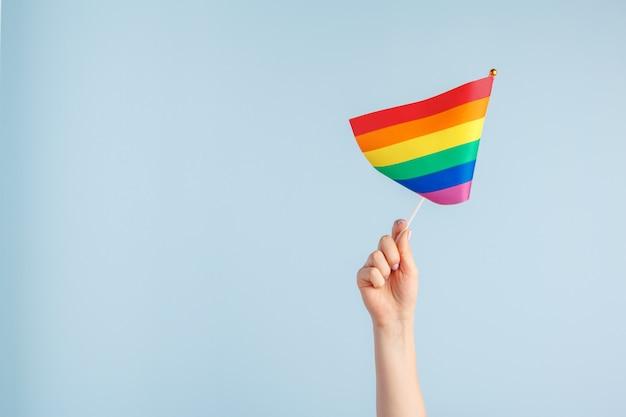 Banderas gay en mano de mujer sobre fondo gris