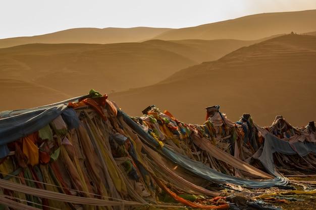 Banderas de oración filas, con hermosas montañas en el fondo de la hora del atardecer, el tíbet