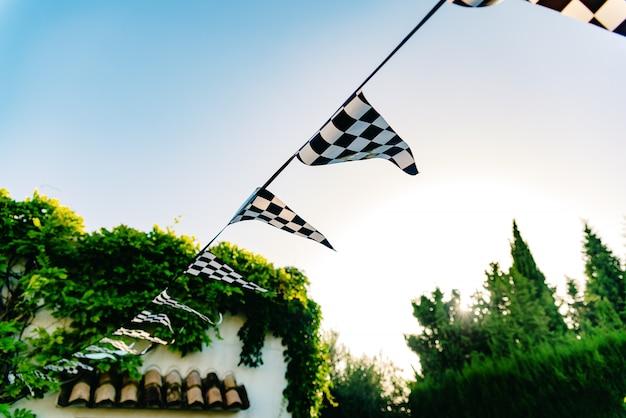 Banderines decorativos colgantes con una bandera a cuadros.