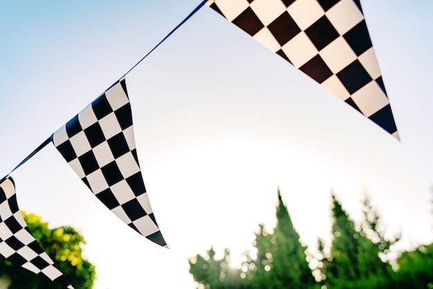 Banderines decorativos con cuadrados en blanco y negro como la bandera de un comisario de carreras de autos.