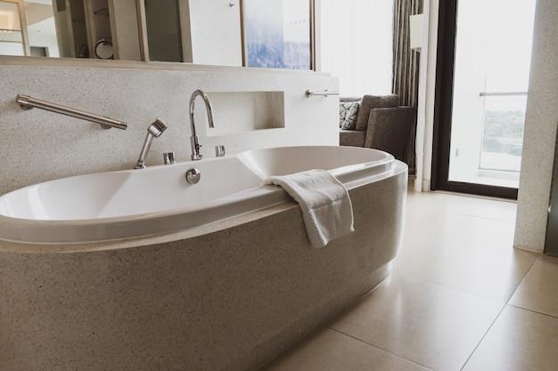 Bañera blanca moderna en baño moderno. hermosa bañera de lujo en tono blanco.