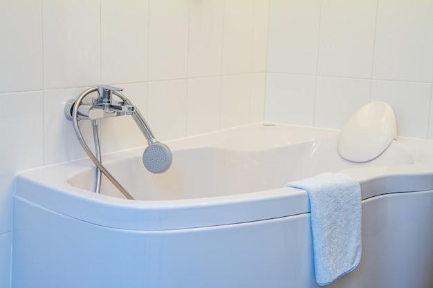 Bañera de esquina moderna con reposacabezas, grifo y ducha con una manguera larga