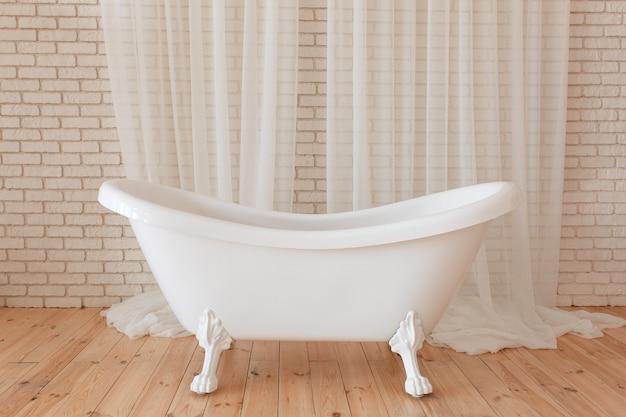 Bañera de lujo de la vendimia en el fondo de ladrillo blanco