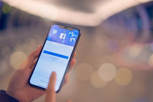 Bangkok, tailandia - 07 de octubre de 2019: la mano está presionando la pantalla de facebook en el iphone de apple, las redes sociales están utilizando para compartir información y redes.