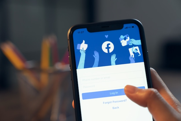 Bangkok, tailandia - 25 de marzo de 2020: la mano sostiene el teléfono y la pantalla de facebook en el iphone de apple, las redes sociales están utilizando para compartir información y redes.