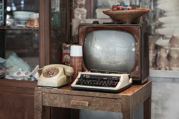 Bangkok, tailandia, 5 de enero de 2020: interior retro - televisor antiguo, máquina de escribir y teléfono de marcación