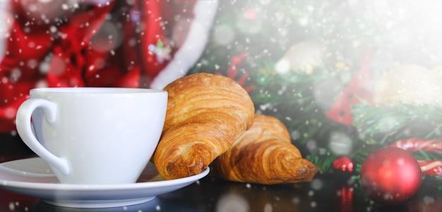 Banner de café de navidad. taza de cristal blanco capuchino caliente con croissants y copyspace