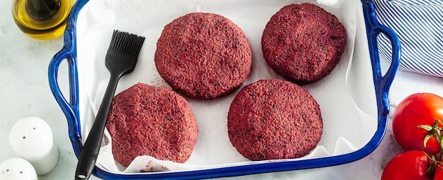 Banner de chuletas veganas crudas para hamburguesa sin carne en una bandeja para hornear sobre una mesa